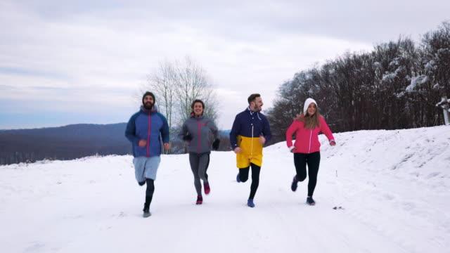 寒い冬の日の間に屋外ジョギングの若い選手たちのグループです。 - 体への関心点の映像素材/bロール