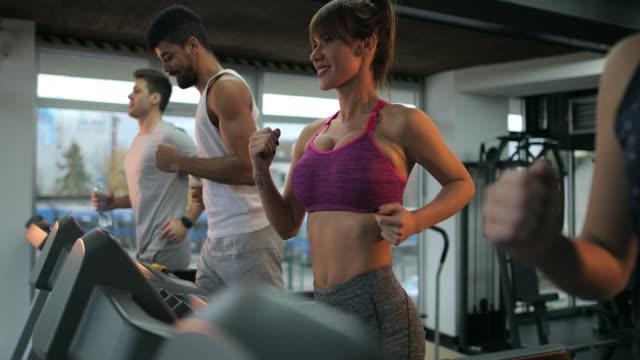 Group of young athletes running on a treadmilsl in a health club. video