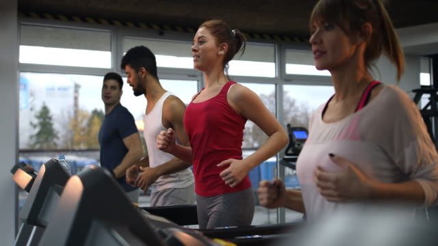 Group of young athletes running on treadmills in a health club. video