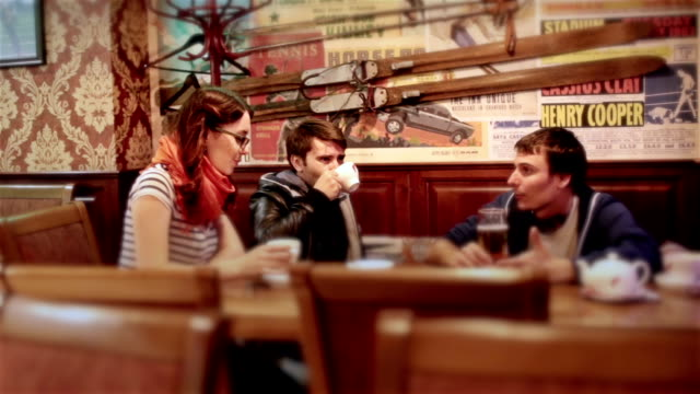Group of young attractive cheerful friends meet in bar. Laughing discussing life video