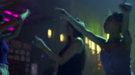 istock Group of young beautiful Asian woman dancing to the music played by dj with drinking alcohol at night club. Pretty girl friend enjoy nightlife and having fun with crazy dance together at disco party 1268395574