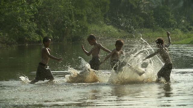 vídeos de stock e filmes b-roll de group of young boy playing water splash with his buffalo on the field.illustrate of a lifestyle of asian developing countries. - sudeste asiático