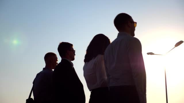 日没時に街を歩いて若いビジネス同僚のグループ。同僚のハードな一日の仕事の後の家に彼の方法であります。太陽フレアの背景で。成功のコンセプトです。スローモーションのすぐ後方を� - 投資家点の映像素材/bロール