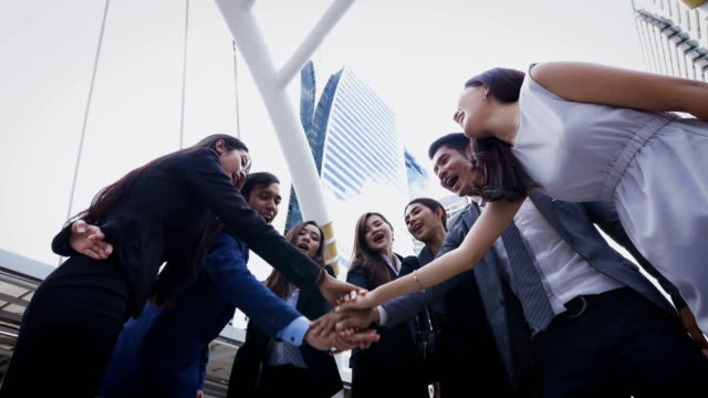 Group of young business people joining hands together outside in modern city, success and team work concept video