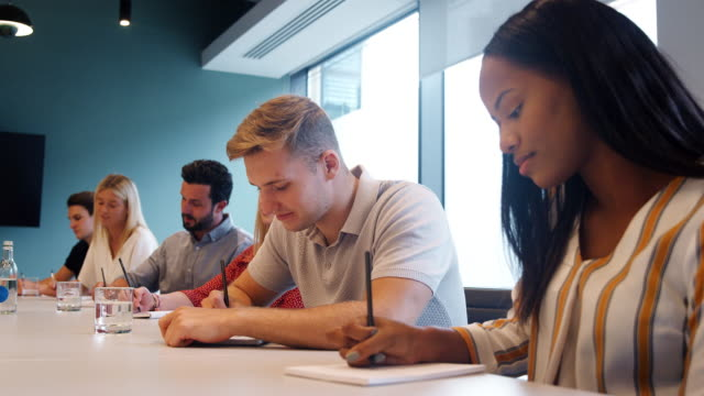 group of young candidates sitting at boardroom table making notes at business graduate recruitment assessment day - apprendista video stock e b–roll