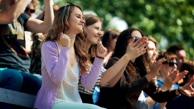 拍手の若い白人ファンのグループ - 観客点の映像素材/bロール