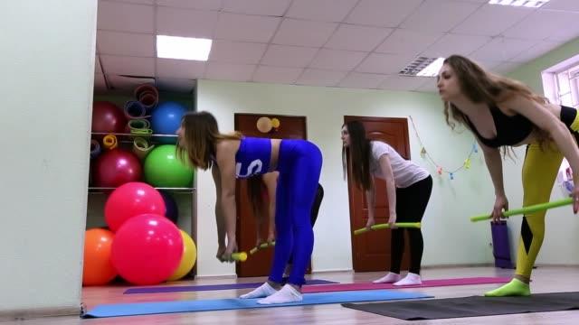 vídeos de stock, filmes e b-roll de grupo de jovens mulheres caucasianos fazendo exercícios com pé de pau no conceito de estilo de vida saudável de estúdio de fitness. - comodidades para lazer