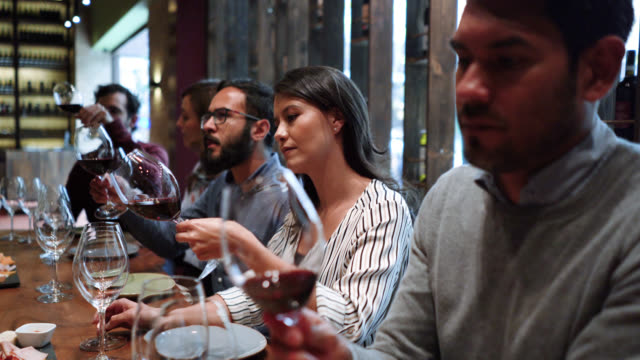 Group of young couples at a wine tasting class learning and moving the wine while looking at it's texture video