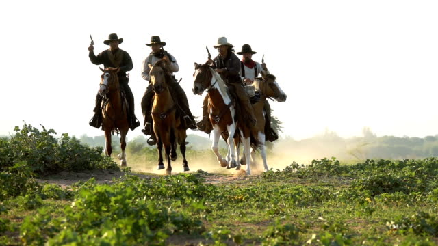 Group Of Young Cowboys Holding Gun And Riding Horse Running In The Meadow Field