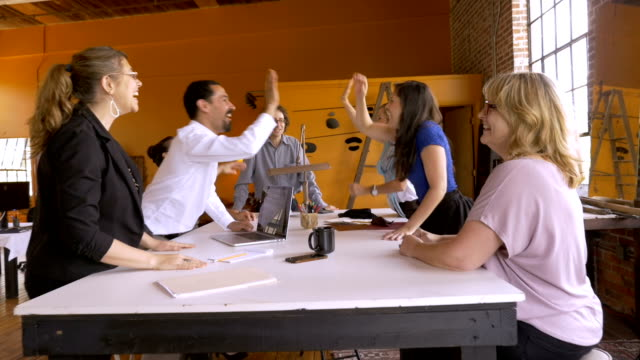 Group of young creative professionals high five celebrating business success video
