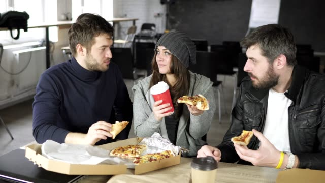 A group of young designers led by the head are working on the project of design office and eating delivered Pizza and drinking tea or coffee in paper cups. Shot in 4k video