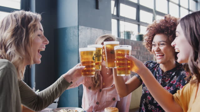 Group of young female friends making a toast with beer as they meet in restaurant bar - shot in slow motion Four Young Female Friends Meeting For Drinks And Food Making A Toast In Restaurant beer stock videos & royalty-free footage
