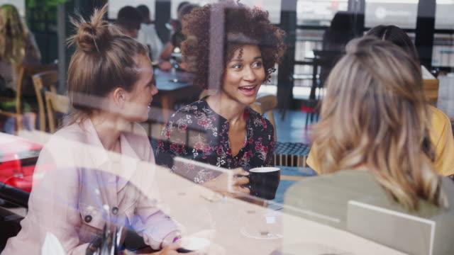 vidéos et rushes de groupe de jeunes amis féminins se rencontrant et s'asseyant autour de la table parlant dans le café tiré par la fenêtre avec des réflexions - projectile au mouvement lent - boisson chaude