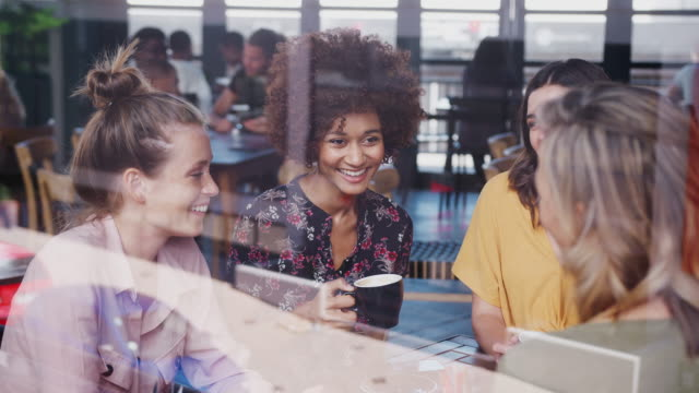 Group of young female friends meeting and sitting around table talking in cafe shot through window with reflections - shot in slow motion Four Young Female Friends Meeting Sitting At Table In Coffee Shop And Talking Viewed Through Window coffee stock videos & royalty-free footage