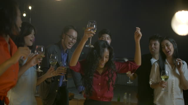 ダンスと楽しい夏屋上パーティーで一緒にクリスマス祭と新年を祝っての若い友人のグループです。スローモーション。 - 飲み会点の映像素材/bロール