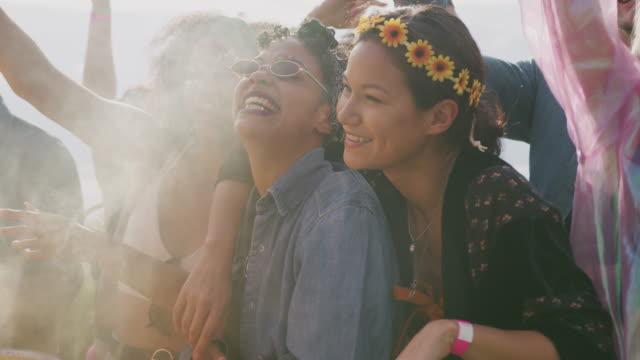 gruppe junger freunde tanzt hinter barrieren auf musikfestivalgelände mit rauchfackel - in zeitlupe gedreht - musikfestival stock-videos und b-roll-filmmaterial