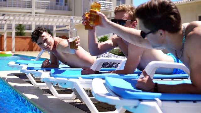 Group of young friends drinking beer and relaxing lying on the coaches by the swimming pool. Slowmotion shot video