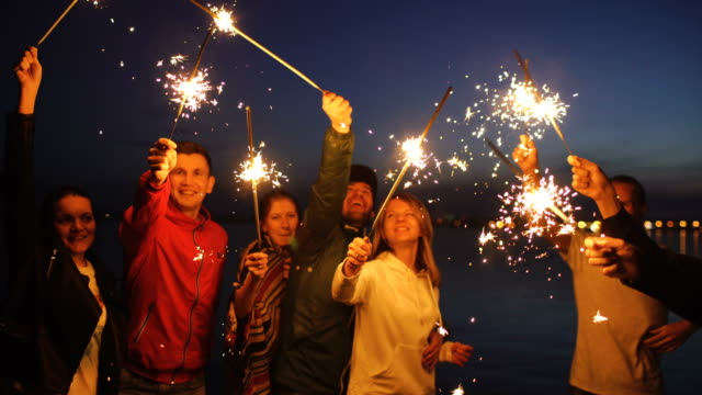 Group of young friends having a beach party. Friends dancing and celebrating with sparklers in twilight sunset - video