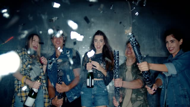 Group of young friends partying with confetti and champagne video