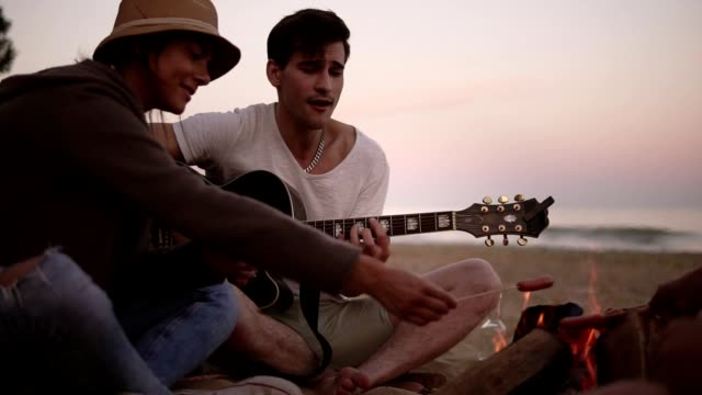 Group of young friends sitting by the fire on the beach, grilling sausages and playing guitar. Slowmotion shot - video