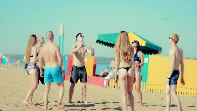 Group of young girls and boys playing beach volleyball video