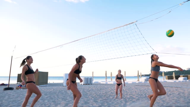 Group of young girls playing beach volleyball during sunset or sunrise, slow motion Group of young girls playing beach volleyball during sunset or sunrise, slow motion volleyball sport stock videos & royalty-free footage