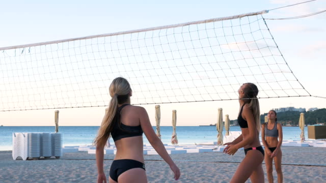 group of young girls playing beach volleyball during sunset or sunrise, slow motion - volleyball stock videos and b-roll footage