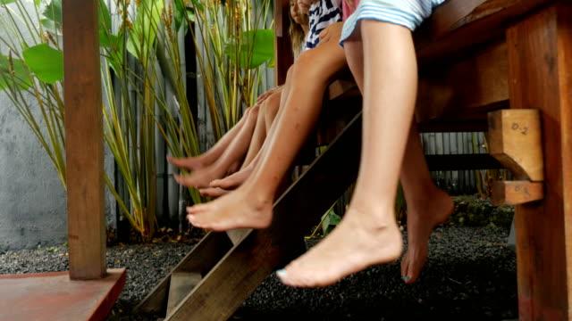 gruppe von jungen mädchen mit nackten füßen schwingen ihre beine, während draußen sitzen - ferienlager stock-videos und b-roll-filmmaterial
