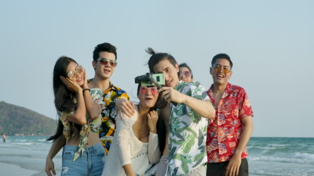 Group of young hipster friends taking selfies on smartphone at the beach in summer vacation. People with travel, holiday and party concept. Slow motion