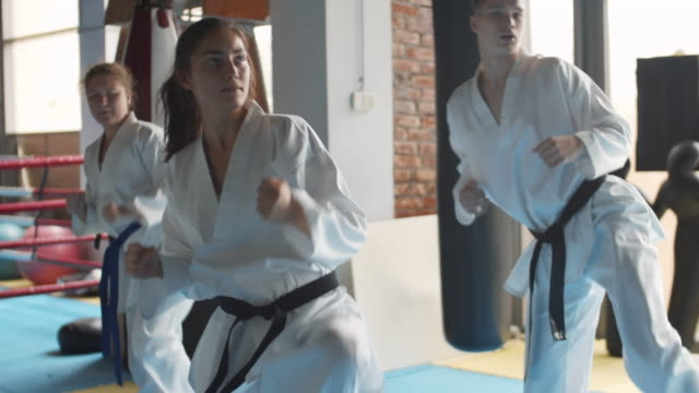 Group of Young Judokas in Gym Pan shot of team of young Caucasian male and female kickboxers practicing kicks and punches in fighting center martial arts stock videos & royalty-free footage