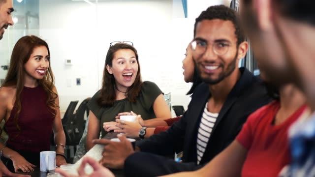 スタートアップ プロジェクトを開発して、一緒にコーヒー ブレークを持つ若いラテン系の新世紀のグループ - お茶の時間点の映像素材/bロール
