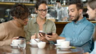 istock Group of Young Mixed race People using Phones in Coffee Shop. 665841764