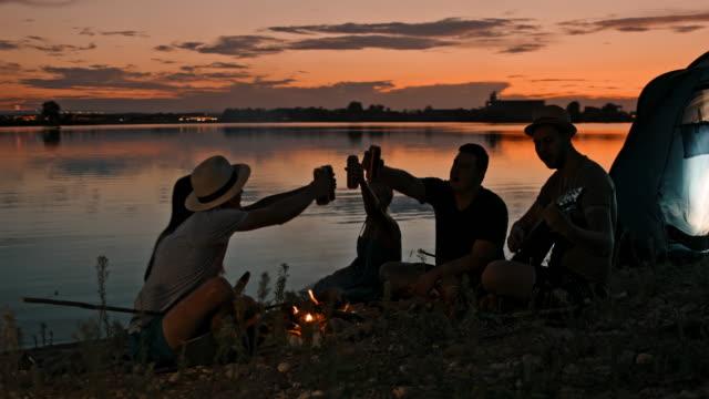 stockvideo's en b-roll-footage met slo mo groep jonge mensen kamperen bij het meer in de schemering - 25 29 jaar