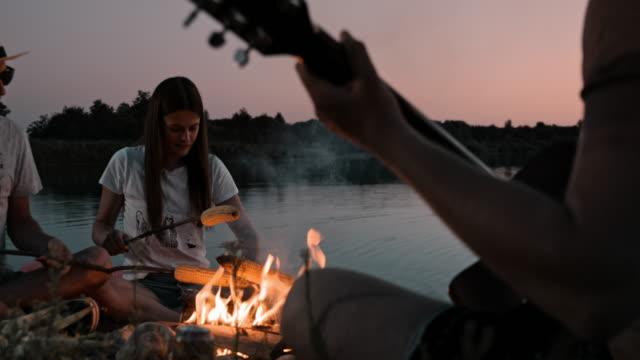 vidéos et rushes de slo mo groupe de jeunes campant au bord du lac - camping