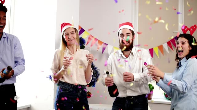 group of young people celebrating christmas and new year in the office opening a bottle of sparkling wine and squib petards with confetti. slowmotion shot - office party stock videos and b-roll footage