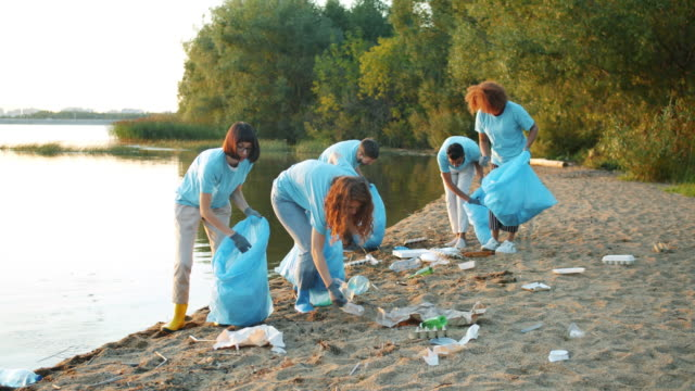 Group of young people collecting waste on river bank cleaning nature from trash