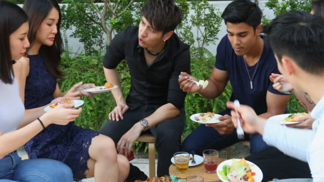 Group of Young People Eating and Making Celebratory Toasts at a Party