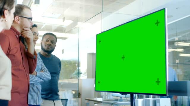 stockvideo's en b-roll-footage met groep jongeren in de conferentieruimte zijn discussie over mock-up chroma key groen scherm tv. - bedrijfsstrategie