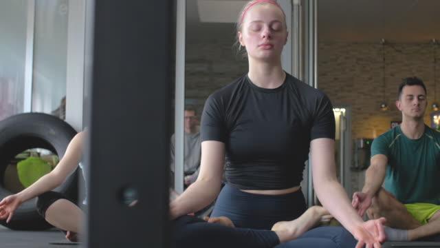 gruppe junger menschen, die in einem yoga-klassenzimmer meditieren - fitnesskurs stock-videos und b-roll-filmmaterial
