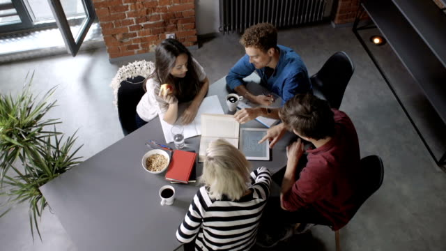 Group of young people on the meeting in modern loft apartment/office. video