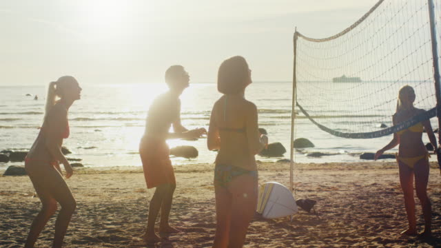 Group of Young People Playing in Beach Volleyball in Sunset Light. Slow motion 60 FPS. ビデオ