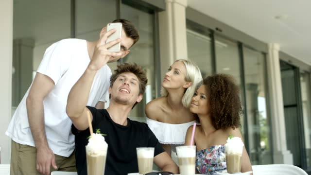 vídeos de stock e filmes b-roll de group of young people sitting in a restaurant and taking a selfies. - café gelado
