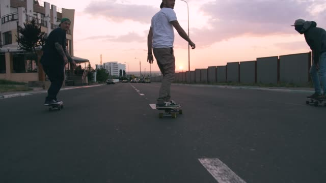 Group of young people skateboarding on the road in the early morning, cinematic shot, slow motion Group of young people skateboarding on the road in the early morning, cinematic shot, slow motion skating stock videos & royalty-free footage