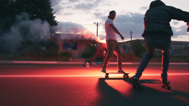 Group of young people skateboarding on the road in the early morningwith red sugnal flare, slow motion video