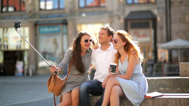 Group of Young People Taking Selfie Using Smartphone Outdoors on the City Square During Sunny Summer Day. Two Girls and One Boy Photorgraphing Themselves by Mobile Phone video