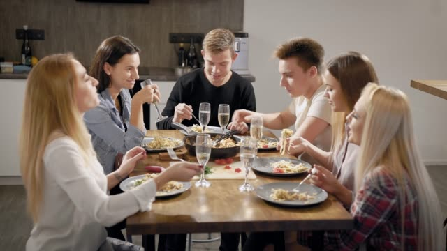group of young roommates are sitting at table and dinning, clicking by wine glasses saying toasts group of young roommates are sitting at table and dinning, clicking by wine glasses saying toasts, celebrating holidays aperitif stock videos & royalty-free footage