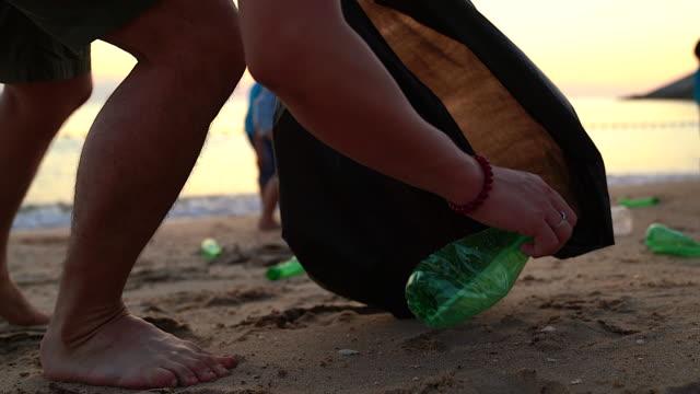 grupp unga frivilliga hjälper till att hålla naturen ren och plocka upp soporna från en sandstrand. - välgörenhet bildbanksvideor och videomaterial från bakom kulisserna