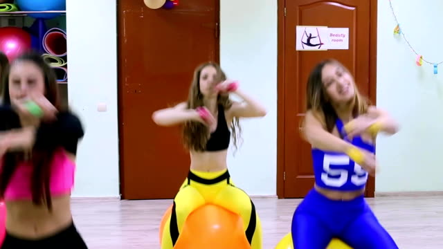 group of young women doing exercises with fitballs and dumbbells in a gym. - donna forzuta video stock e b–roll