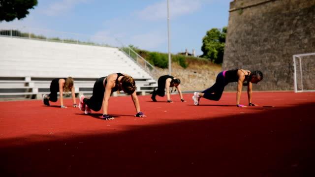 stockvideo's en b-roll-footage met groep jonge vrouwen trainen aërobe buitenshuis - fitnessleraar