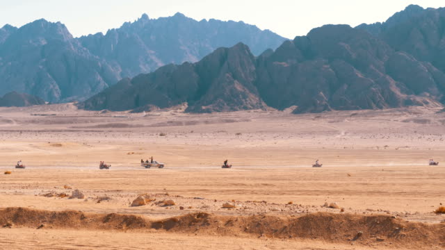 Group on Quad Bike Rides through the Desert in Egypt on backdrop of Mountains. Driving ATVs